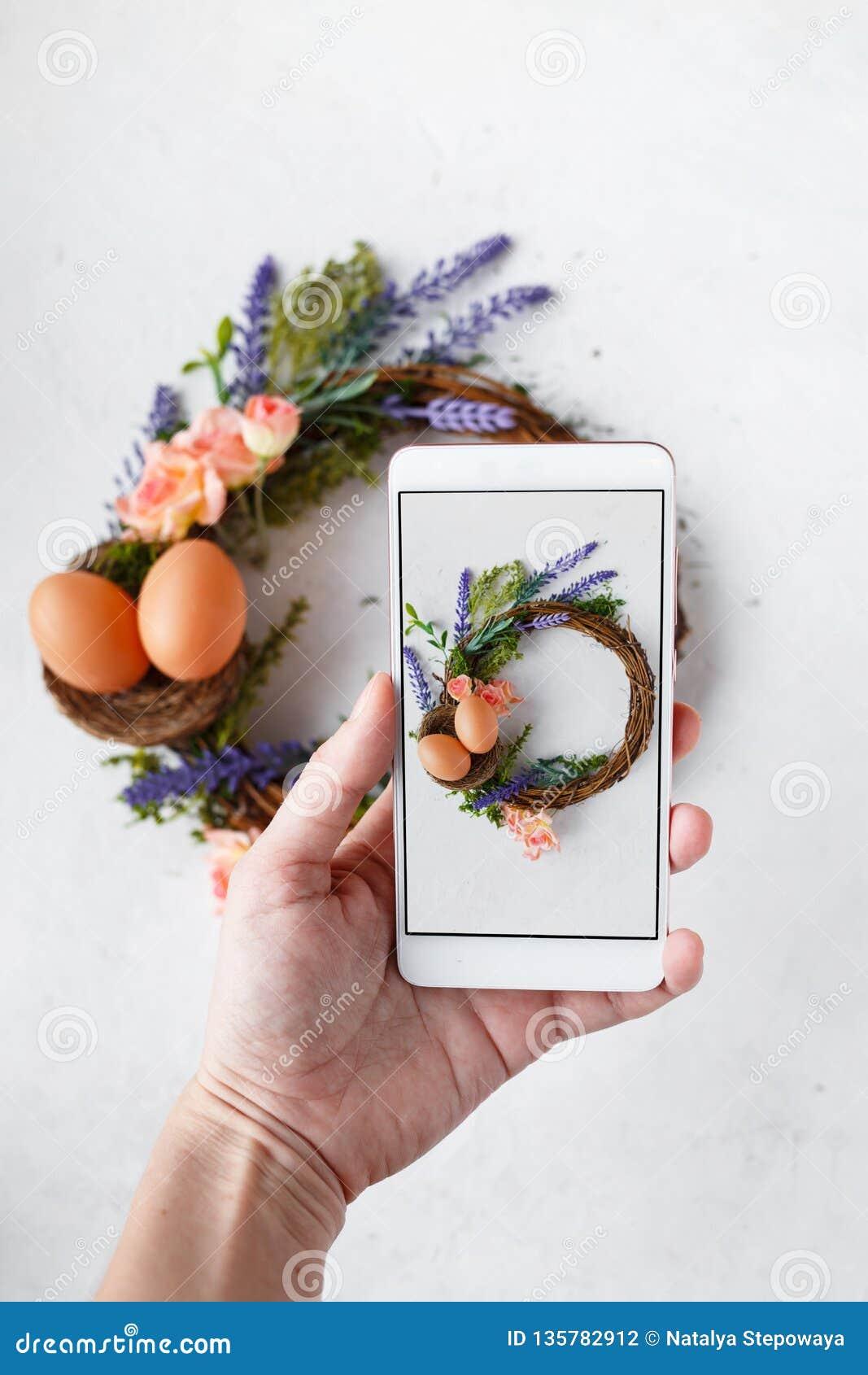 有电话照片复活节花圈的与明亮的春天花,巢女性手用复活节彩蛋