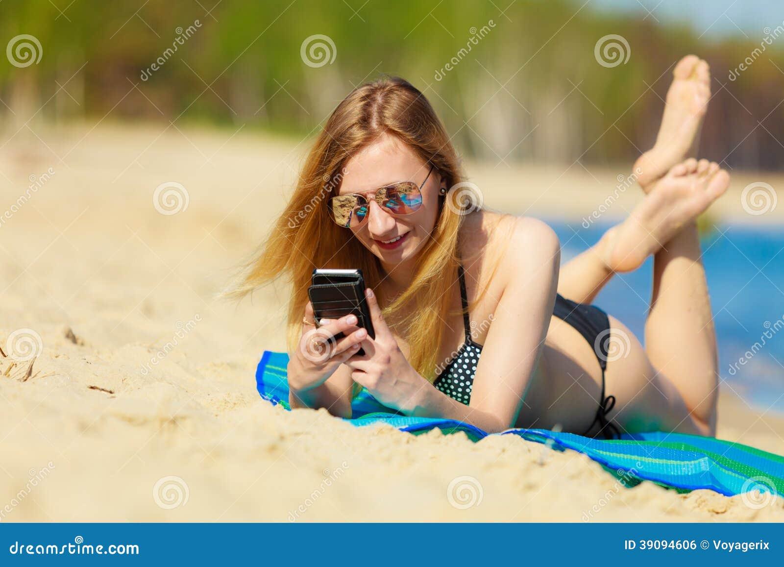 有电话的暑假女孩晒黑在海滩的