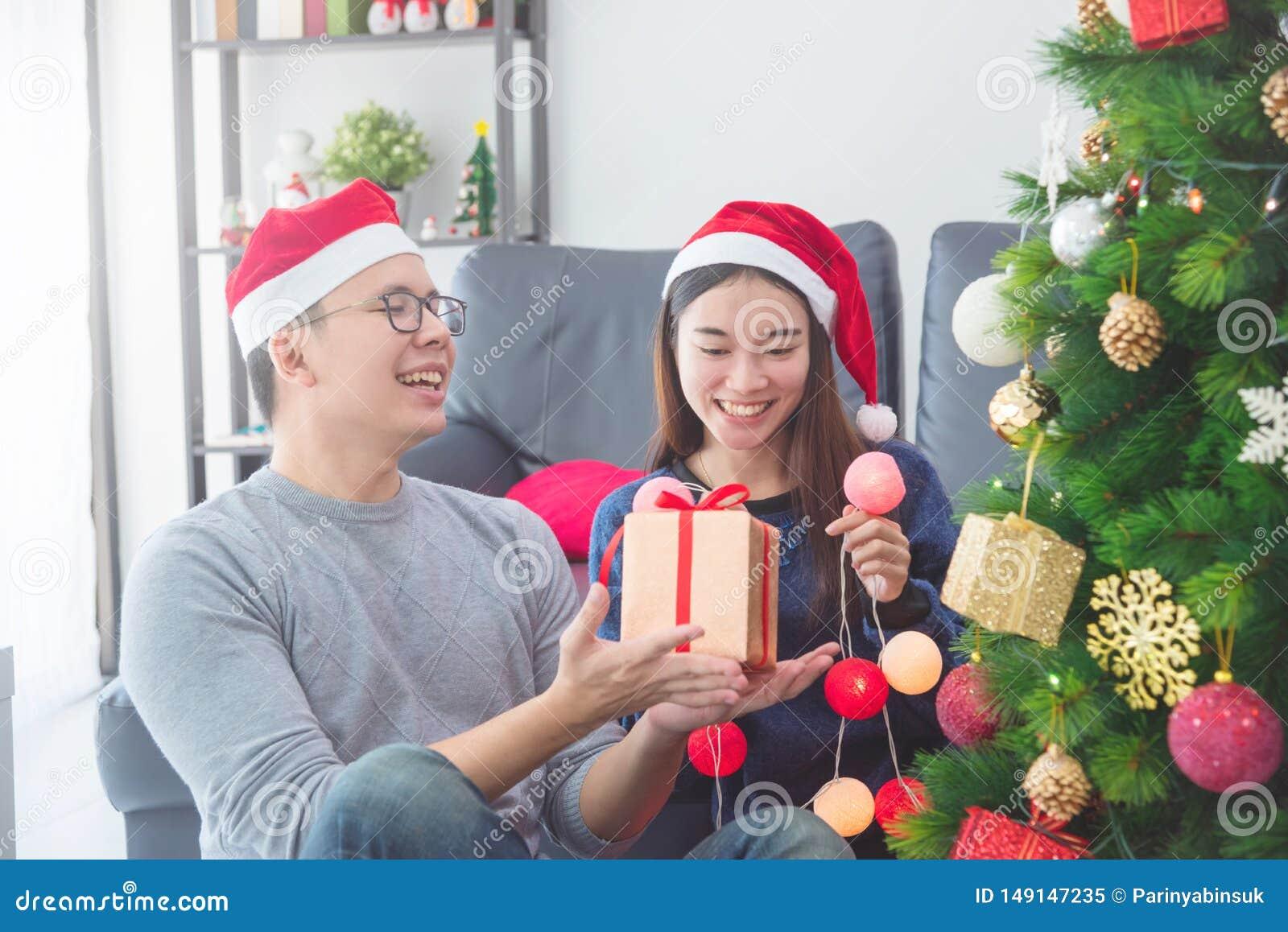 有男朋友的女孩戴圣诞老人帽子在家装饰圣诞树的假日
