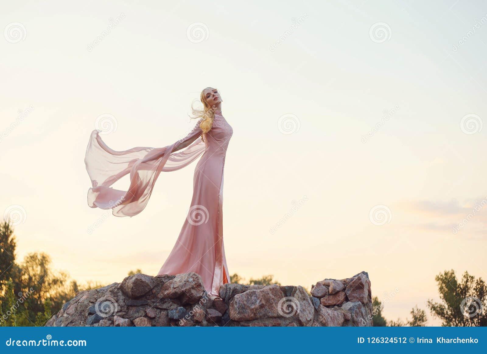 有白肤金发的公平的波浪发的典雅的公主有对此的冠状头饰的,佩带一长浅粉红色起来了振翼的礼服,站立