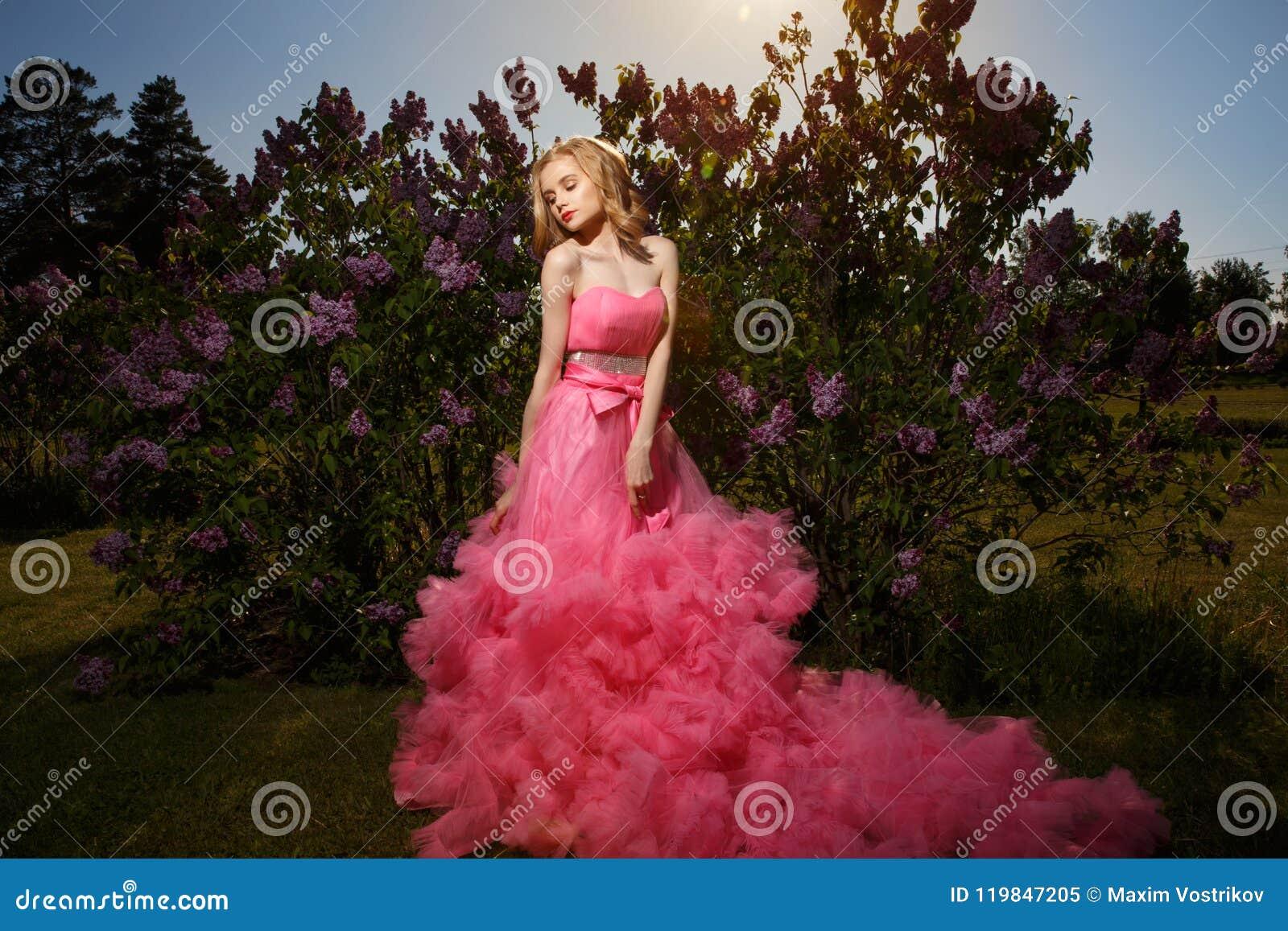 有白肤金发的波浪发的美丽,壮观的穿与蓬松裙子的女孩和构成桃红色晚礼服摆在得户外