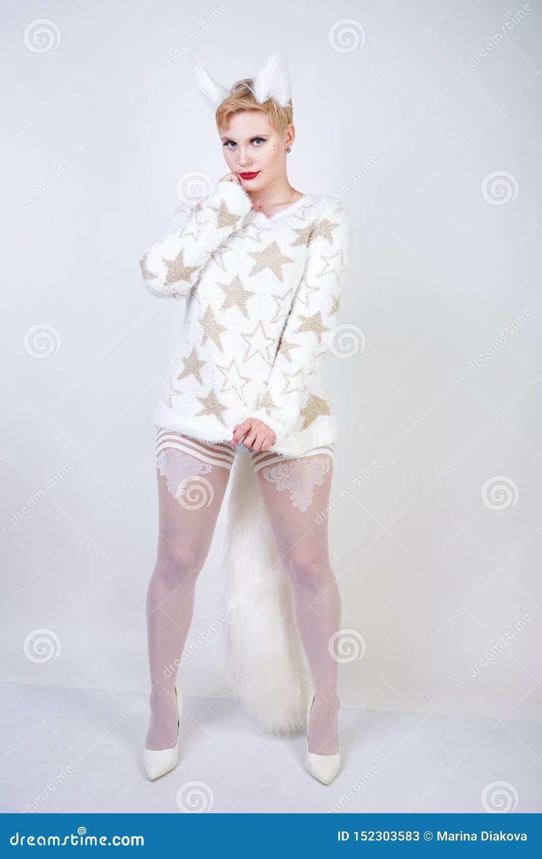 有白肤金发的短发和弯曲的正大小身体佩带的白色毛线衣的俏丽的逗人喜爱的亲切的女孩有金黄星和蓬松毛皮猫的e