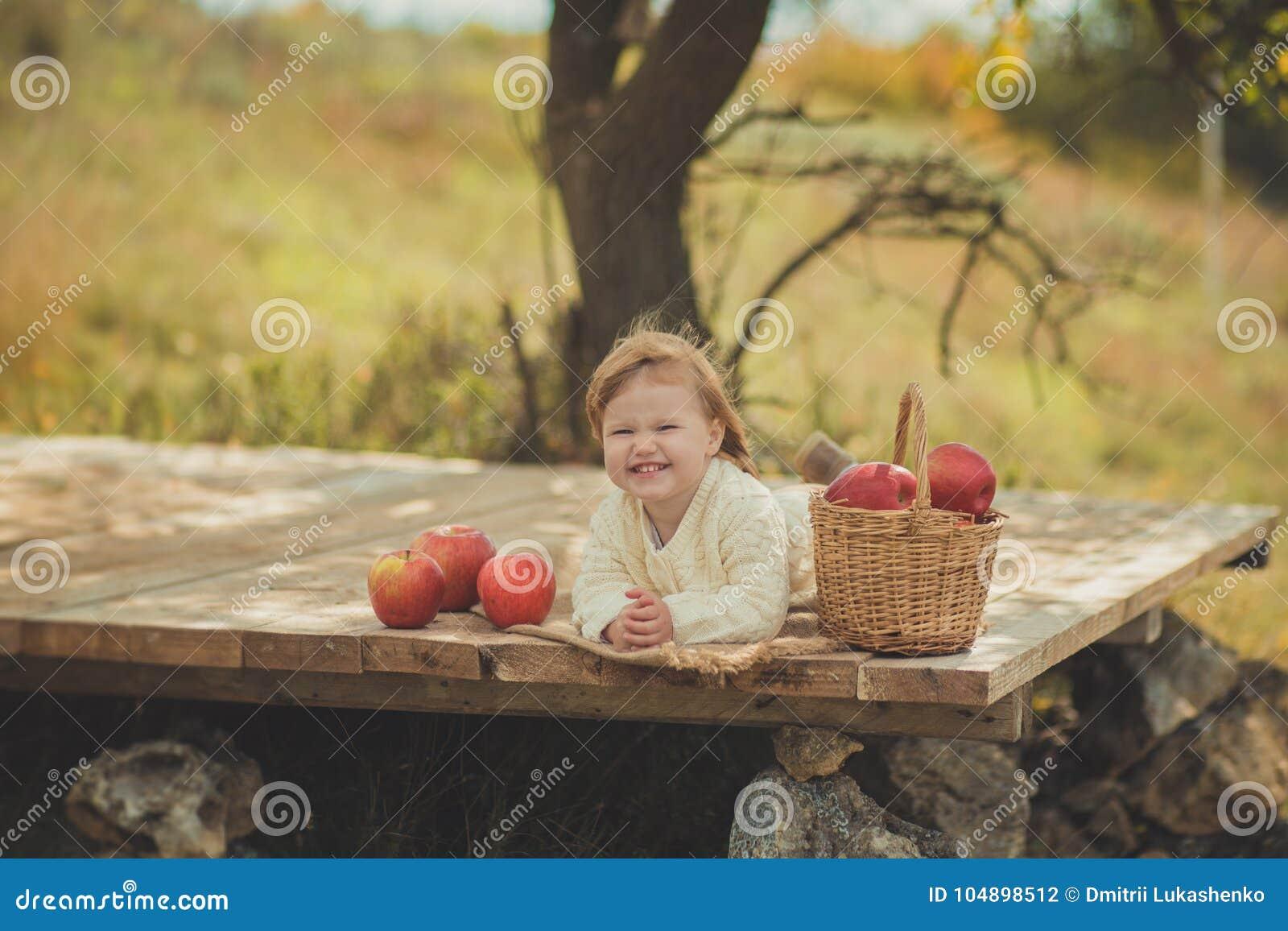有白肤金发的红色头发佩带的象牙颜色白色毛线衣的可爱的俏丽的女婴在城市木的郊区村庄享受生活时间