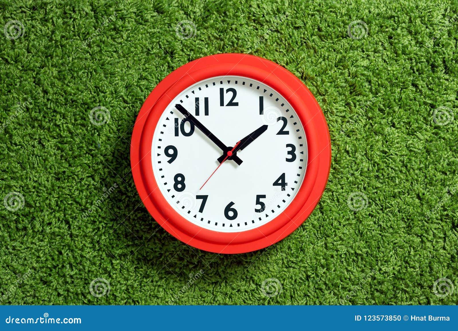 有白色拨号盘的红色时钟在绿色地毯