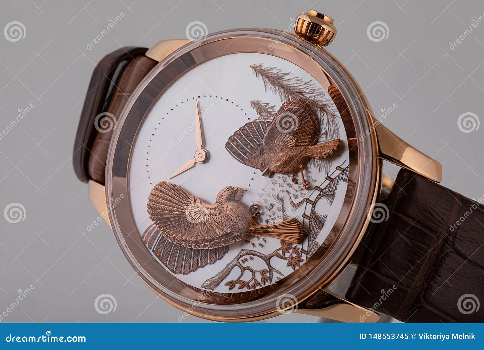有白色拨号盘的金黄手表有顺时针方向样式的,金黄,在白色背景的棕色皮带