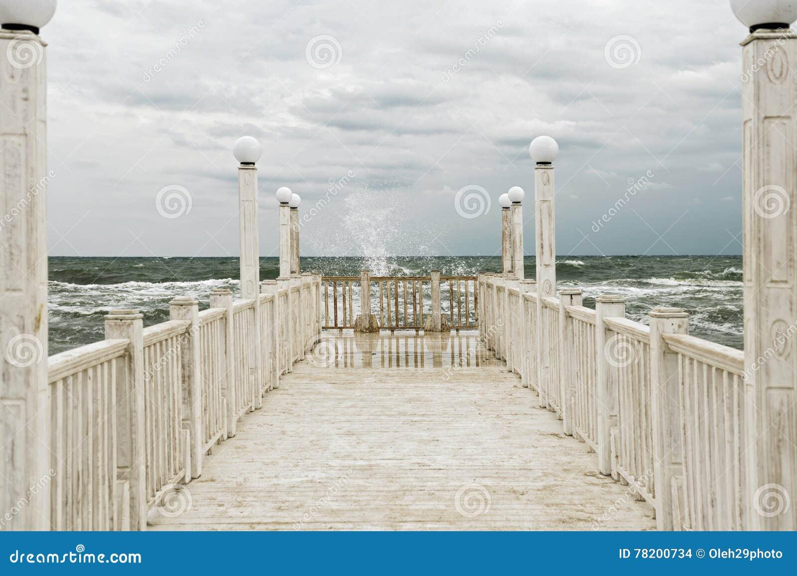 有白色木扶手栏杆的码头海上在风暴期间的