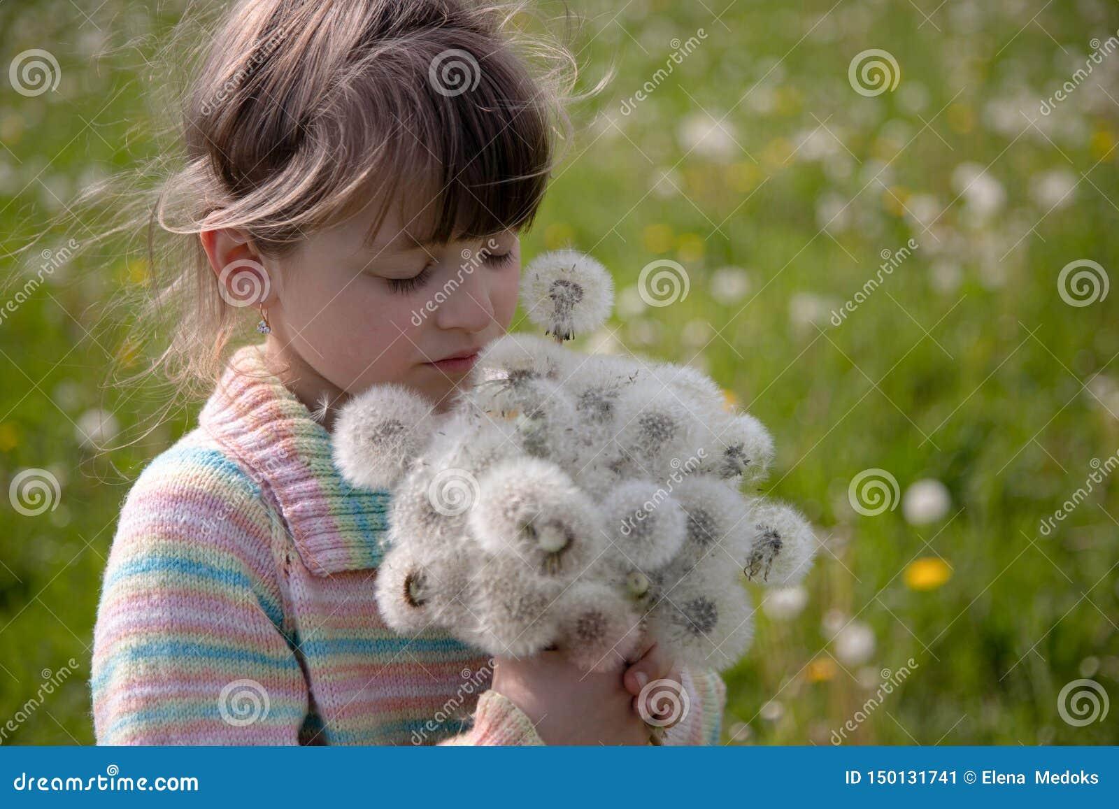 有白色蒲公英花束的美女在春天草甸的