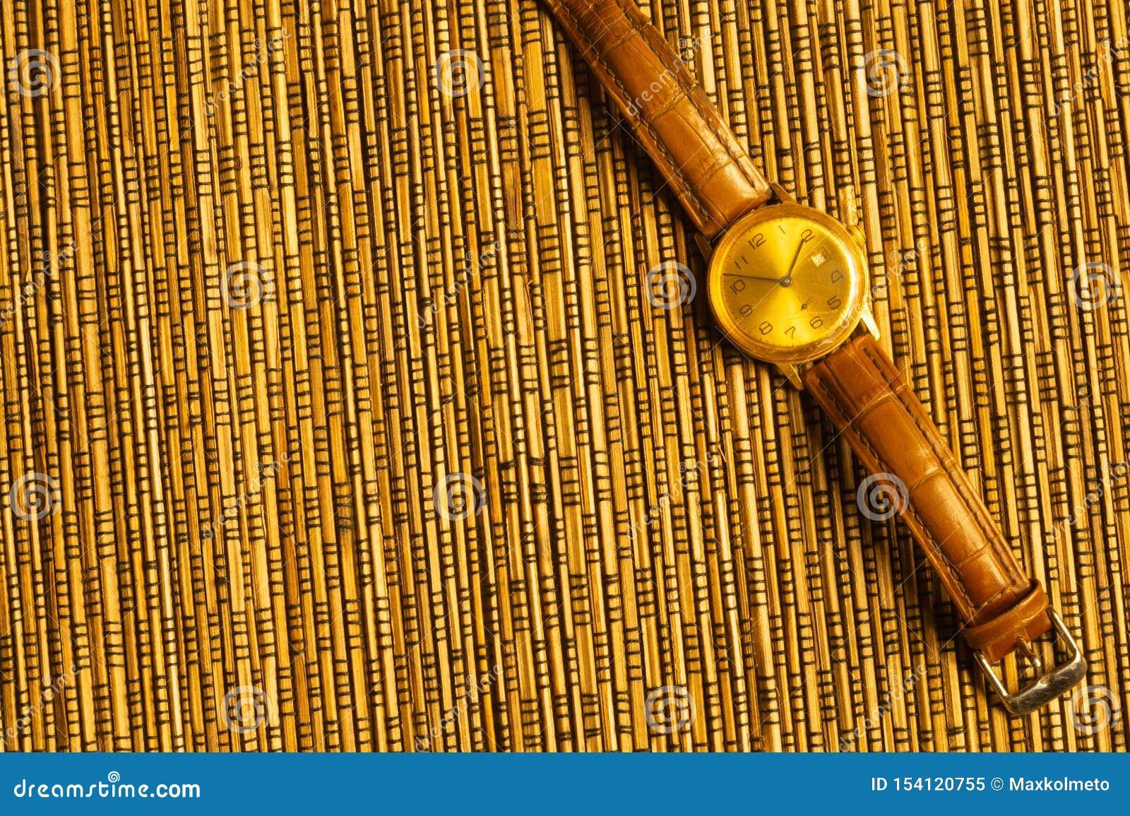 有皮带的葡萄酒金黄手表在竹背景