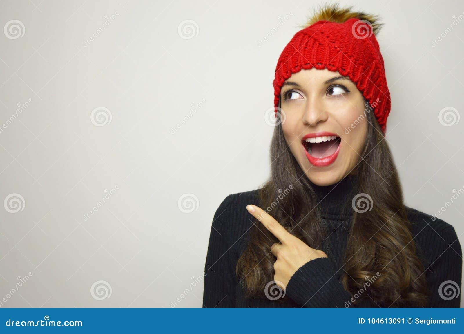 有看对边和指向与她的手指您的在灰色背景的红色帽子的愉快的冬天妇女产品 复制空间