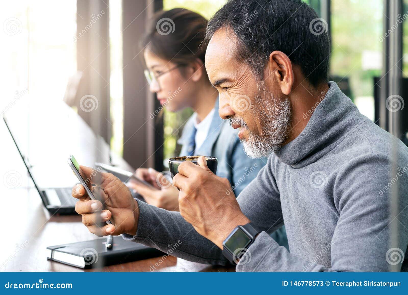 有看智能手机读书新闻或社会媒介与少年的白色时髦的短的胡子hispter的可爱的成熟亚裔人