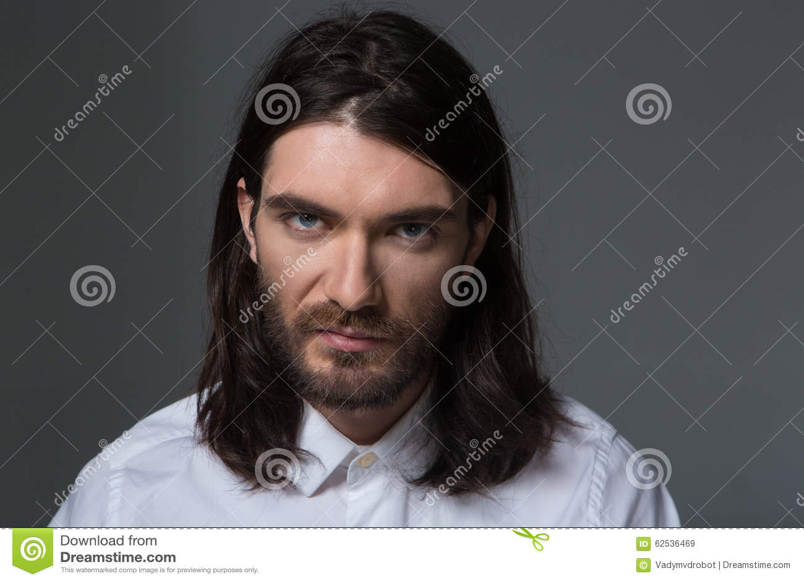 有看照相机的胡子和长的头发的严肃的人