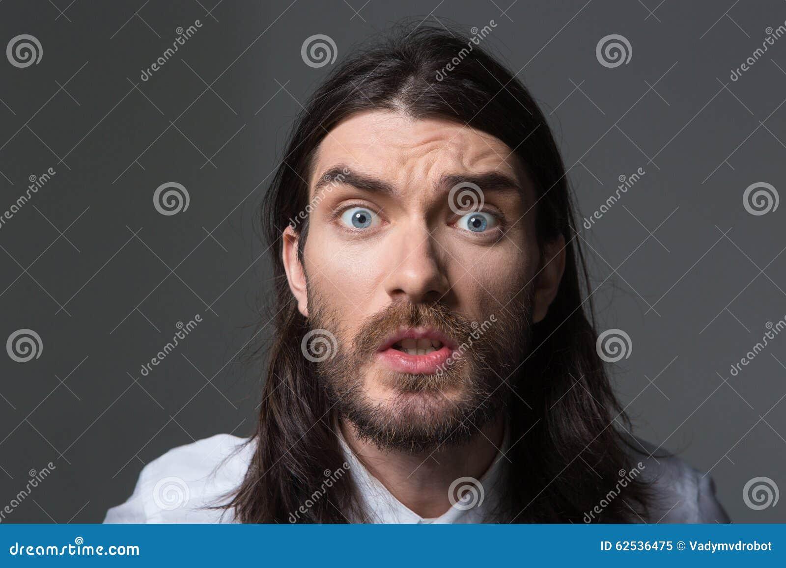 有看照相机的胡子和长的头发的恼怒的人