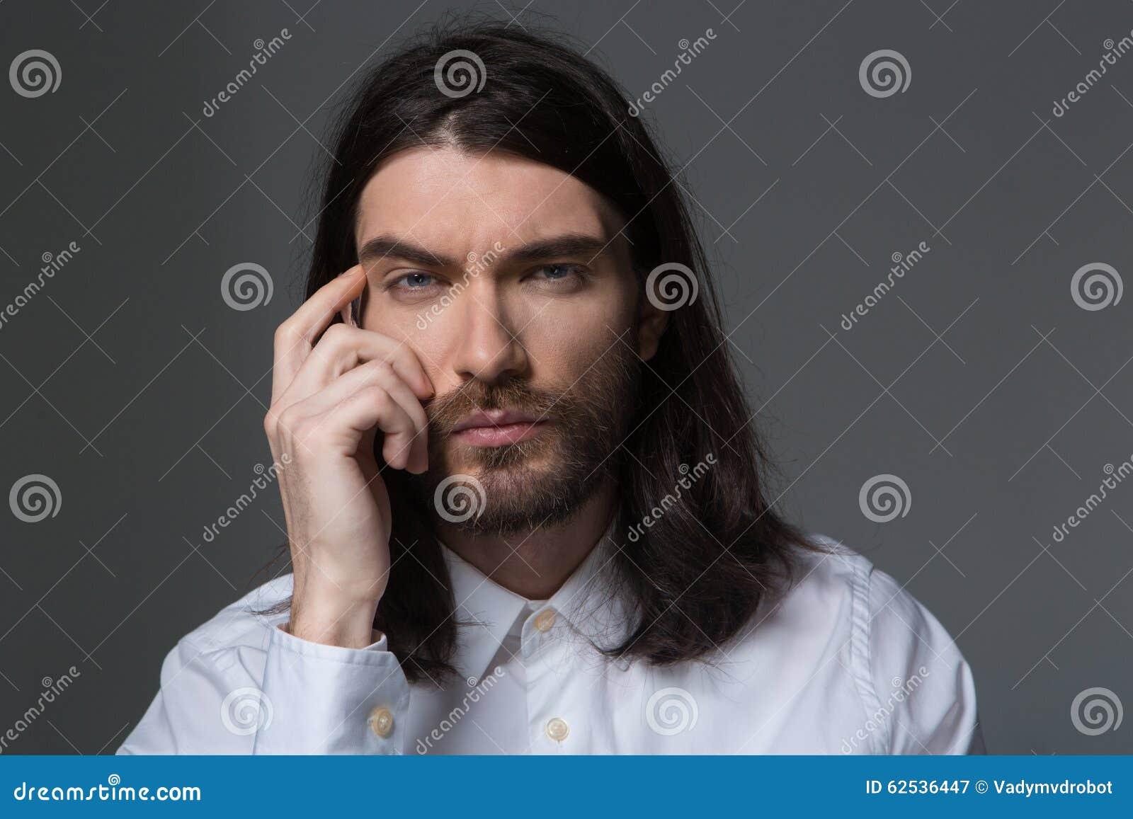有看照相机的胡子和长的头发的沉思人