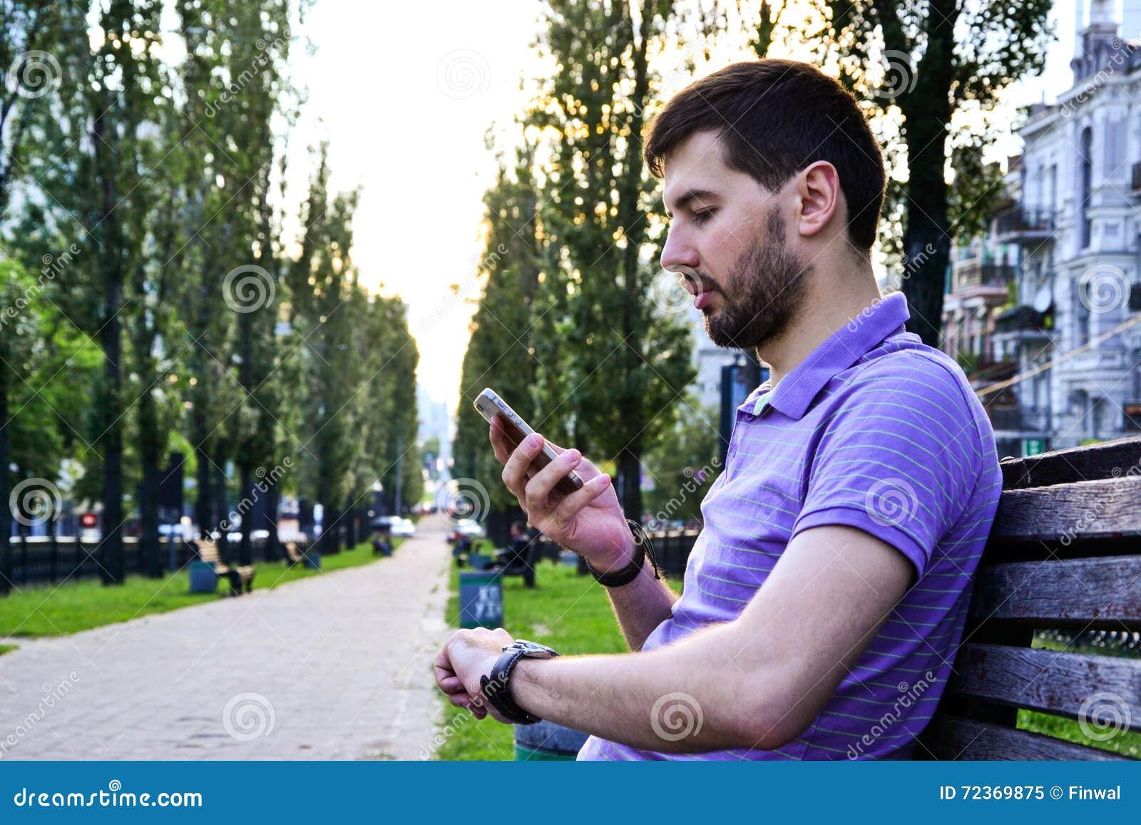 有看电话的手表的繁忙的年轻人户外