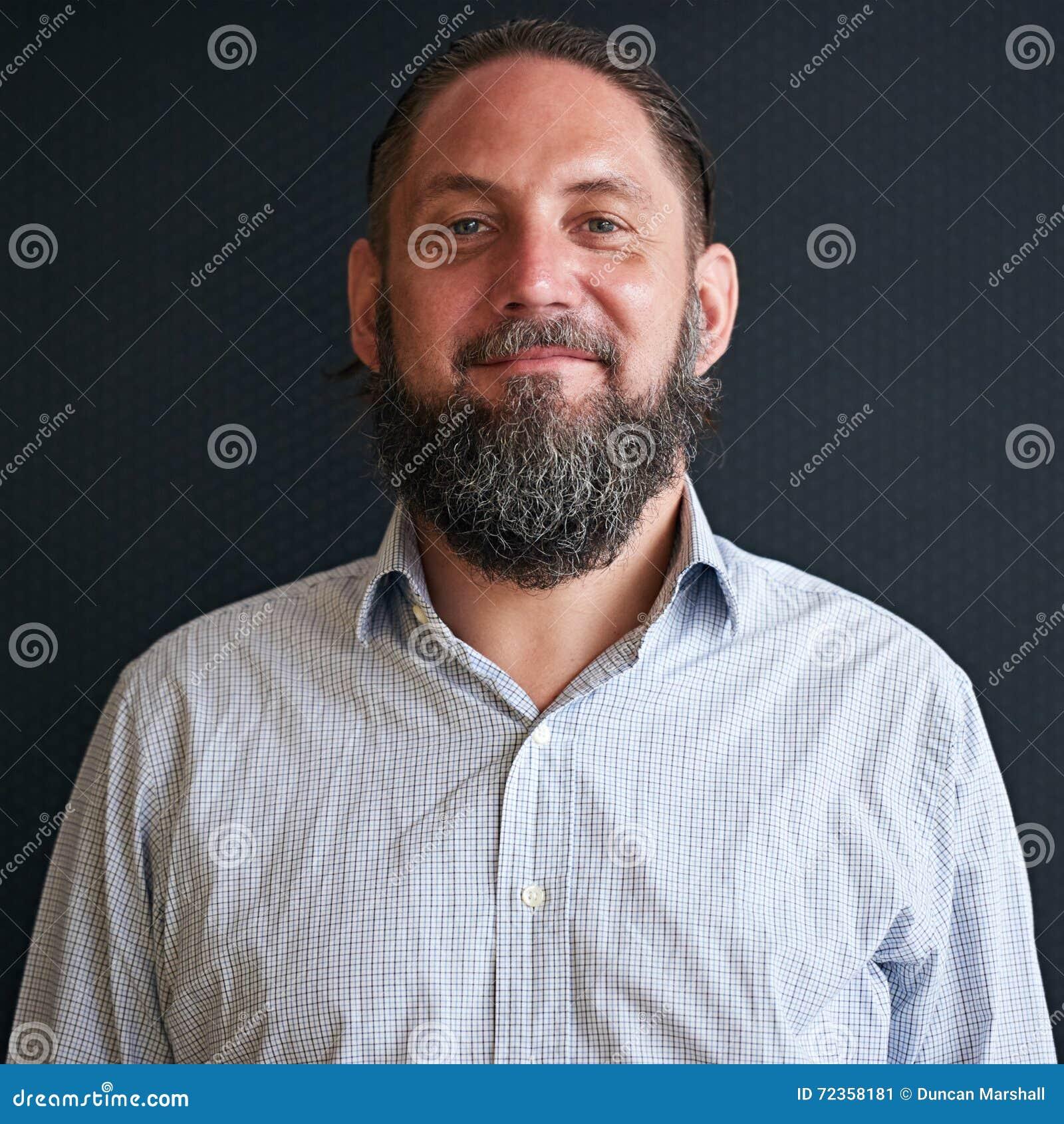 有看直接照相机的胡子的更老的人,当微笑时