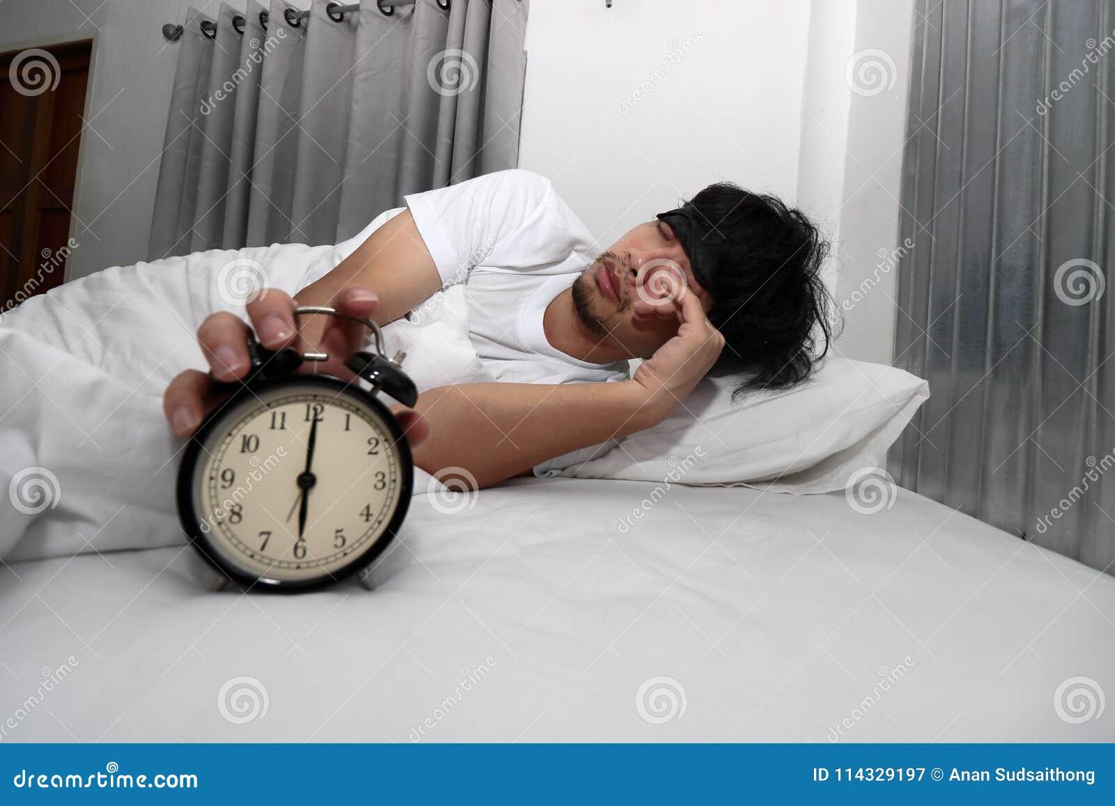 有眼罩的年轻亚裔人叫醒并且停止在床上的闹钟