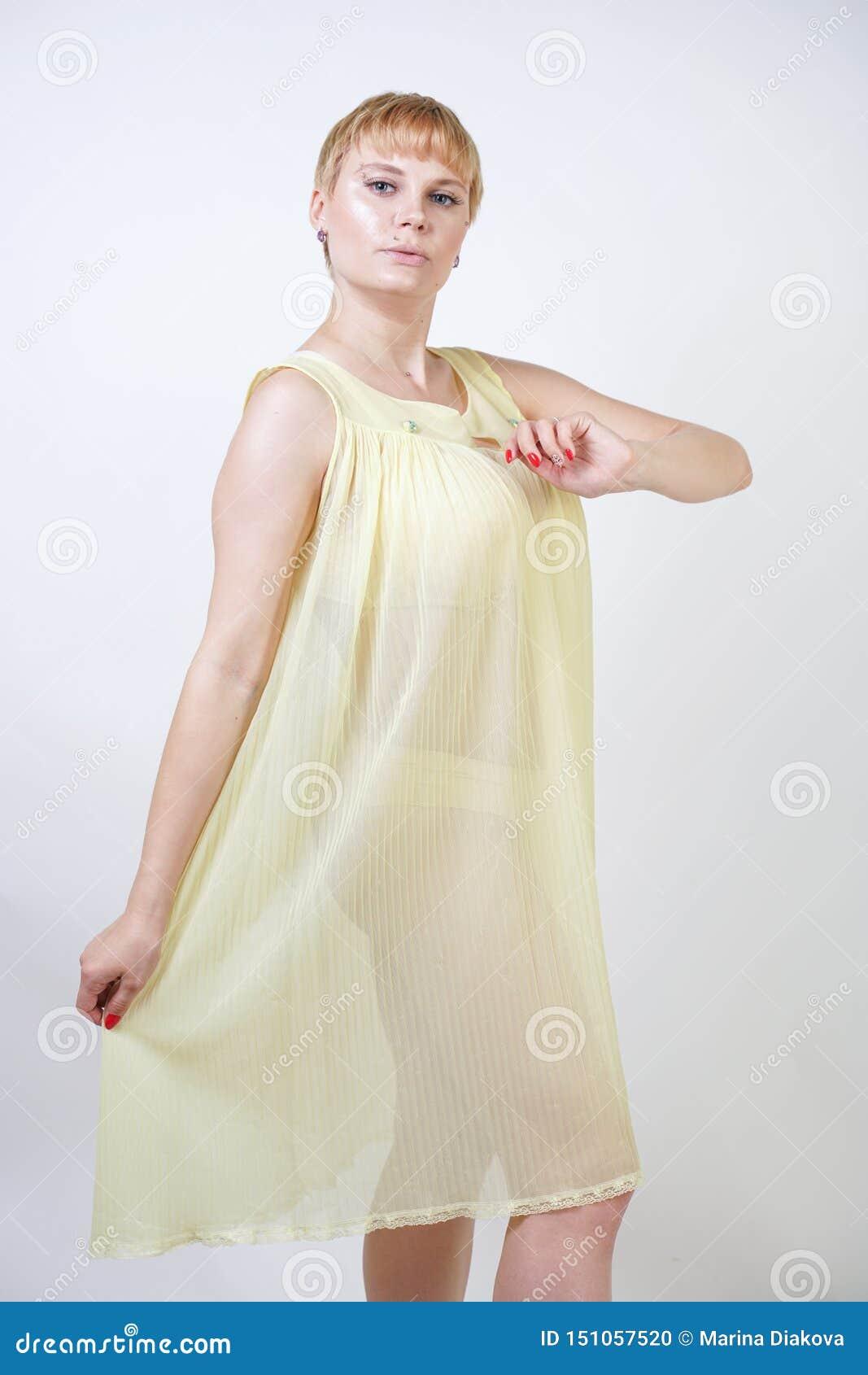 有短发的俏丽的年轻女人和穿透明女睡袍和摆在单独白色演播室背景的胖的身体 ??