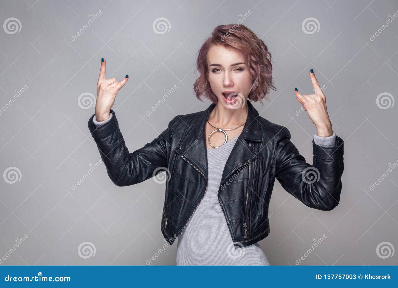 有短的发型和构成的美丽的滑稽的惊奇摇摆物女孩在与岩石标志的便装样式黑皮夹克身分
