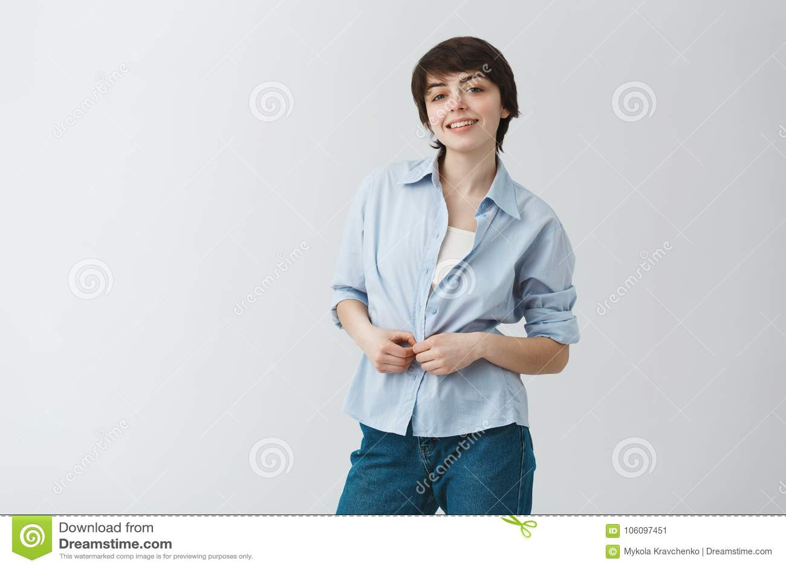 有短的黑发的逗人喜爱的年轻女学生brightfully微笑,按衬衣和看在照相机的以愉快