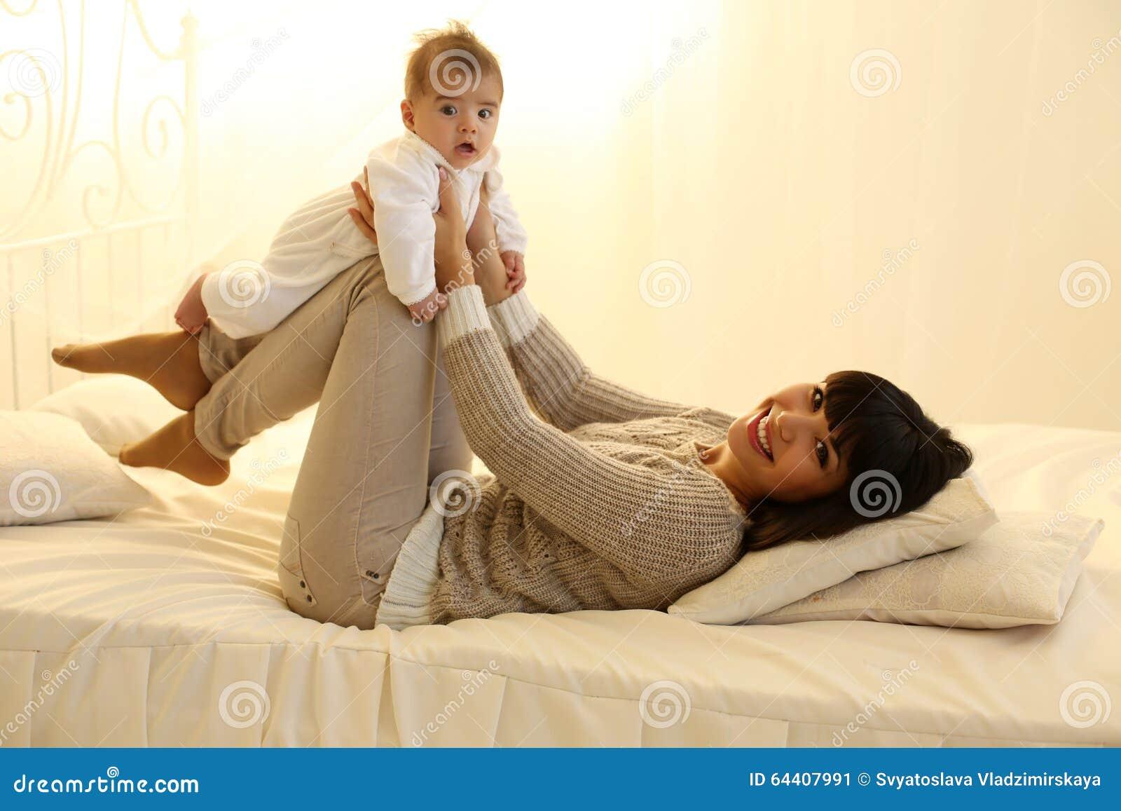 有短的黑发和她的小逗人喜爱的男婴的美丽的母亲