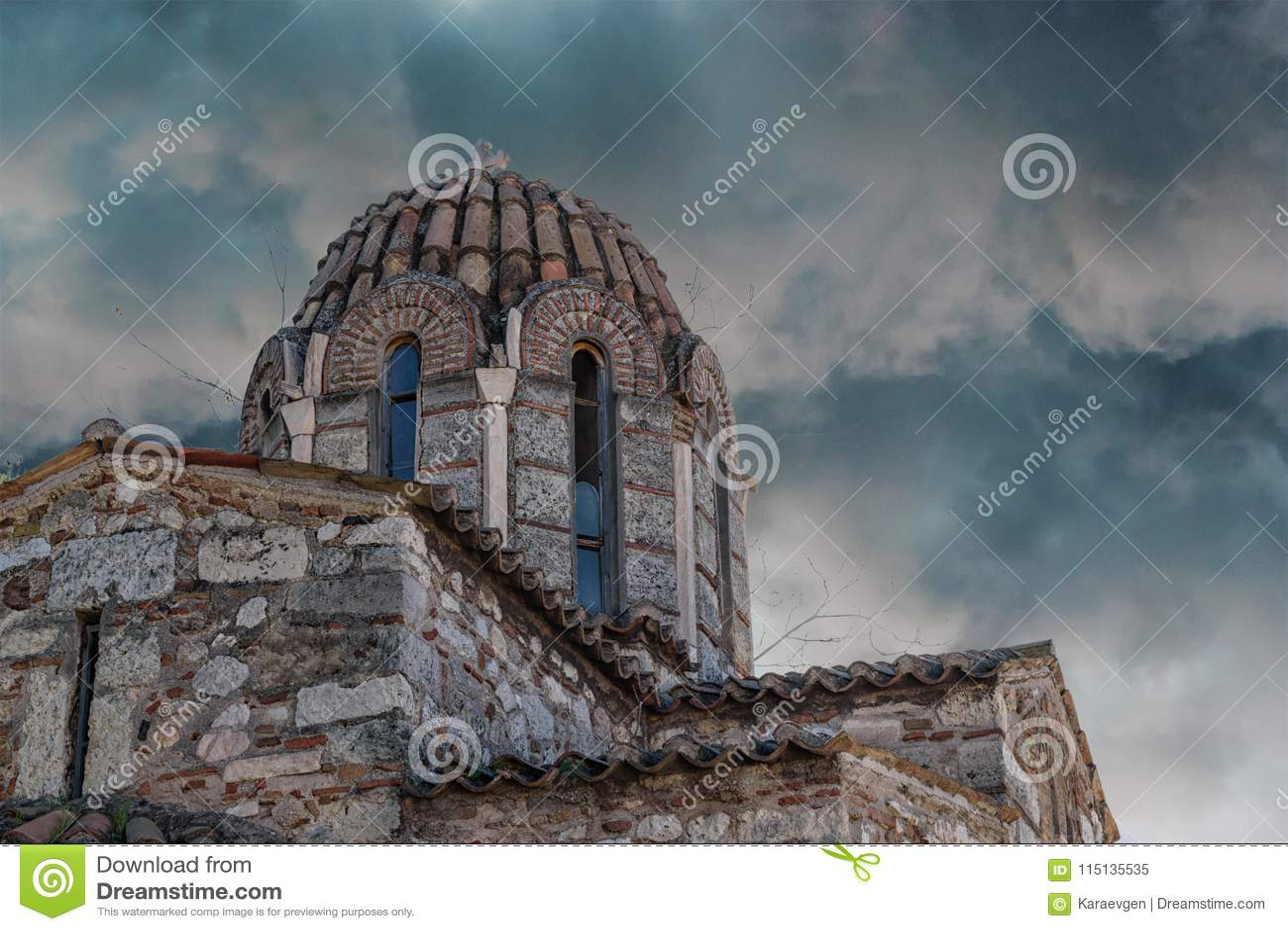 有石十字架的老希腊教会在黑暗的天空背景