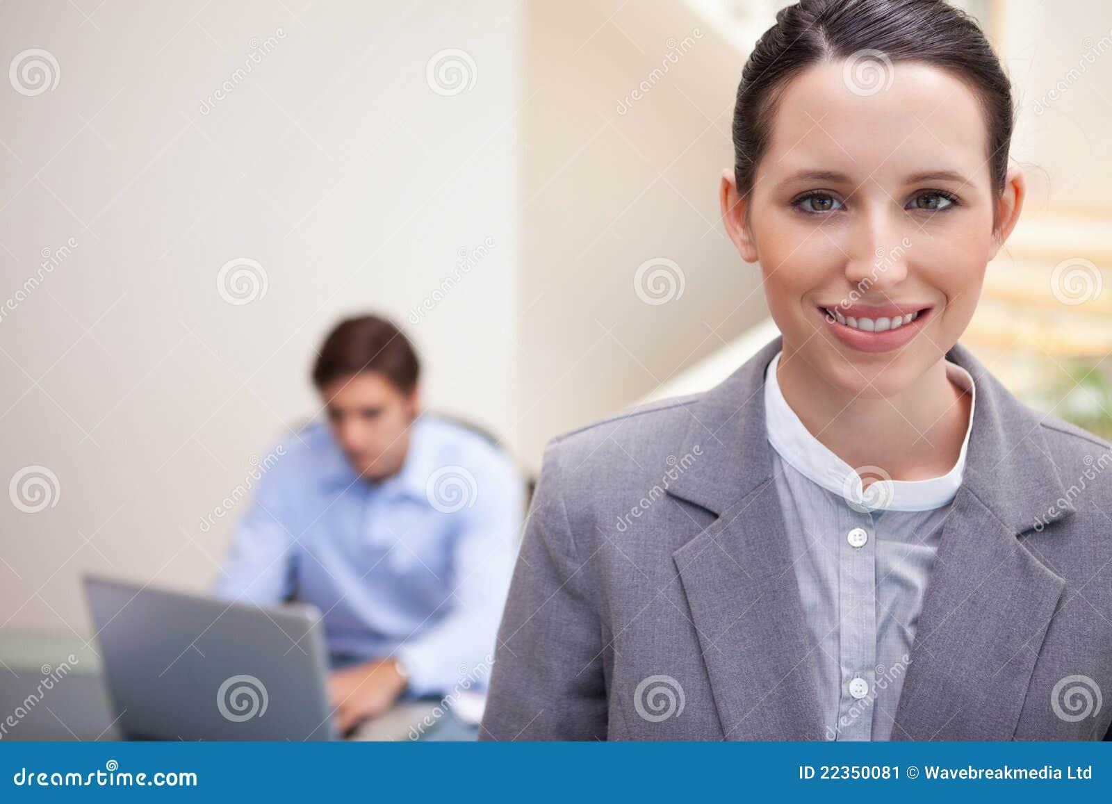 有研究他的膝上型计算机的同事的微笑的女实业家