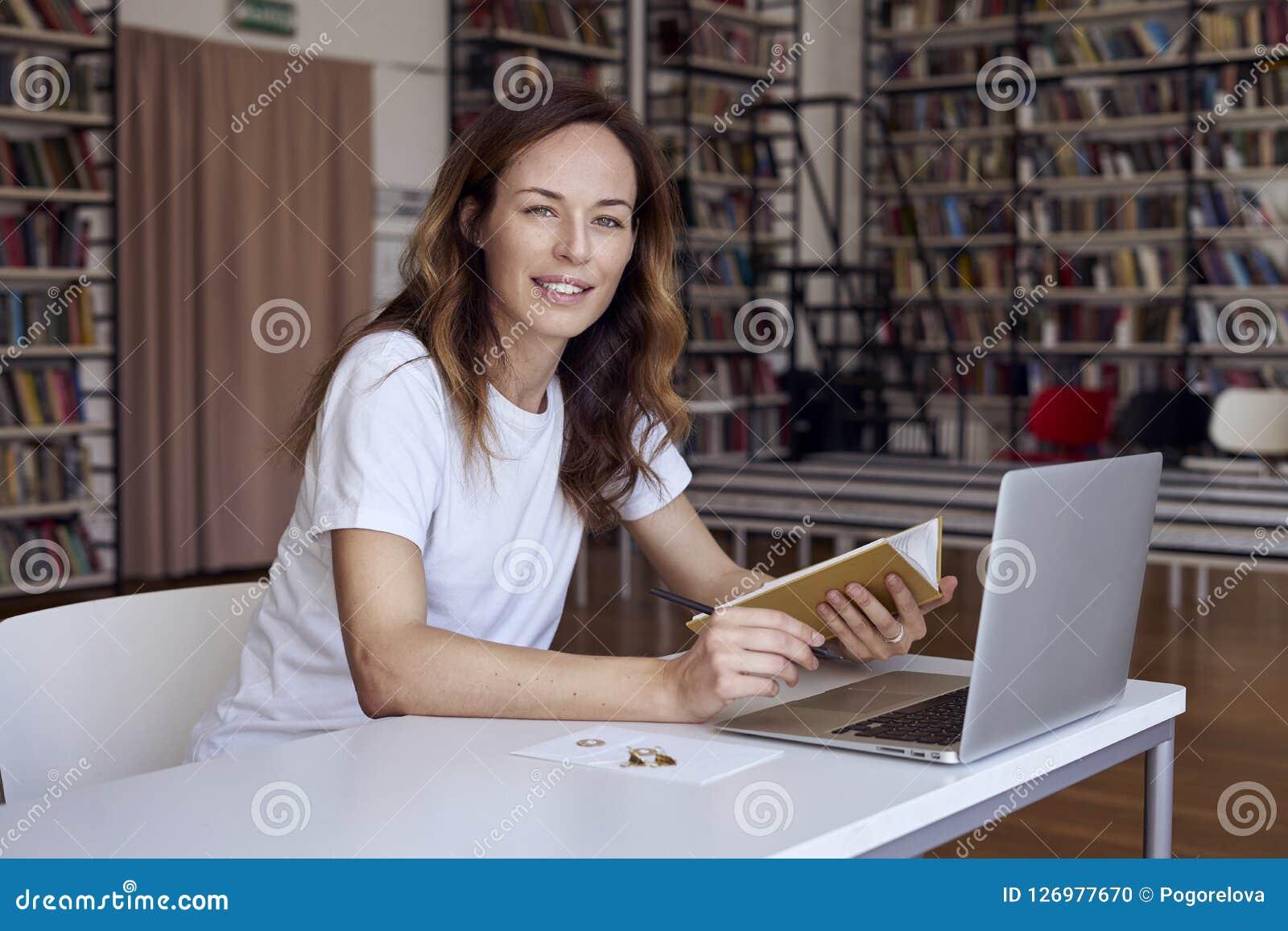 有研究膝上型计算机的长的头发的少妇在共同工作的办公室或图书馆,书架后边 拿着书在手上 女实业家