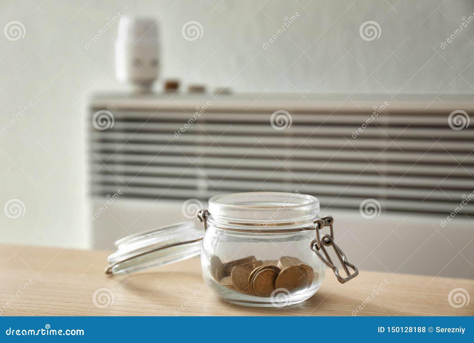 有硬币的瓶子在calorifer附近在家 加热的保存的概念
