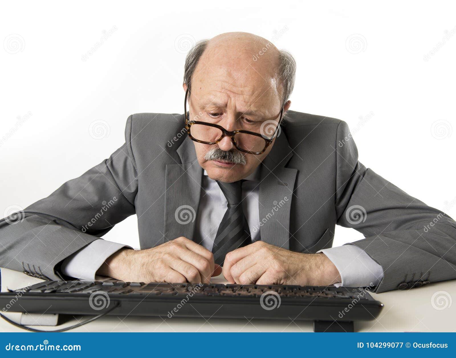 有秃头的商人在他的60s工作被注重和被挫败在办公计算机看起来膝上型计算机的书桌疲乏
