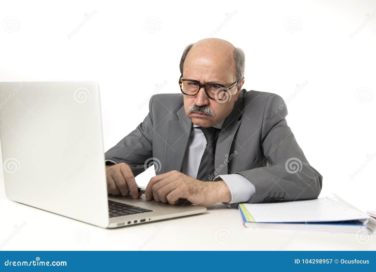 有秃头的资深成熟繁忙的商人在他的60s工作被注重和被挫败在办公计算机看a的膝上型计算机书桌