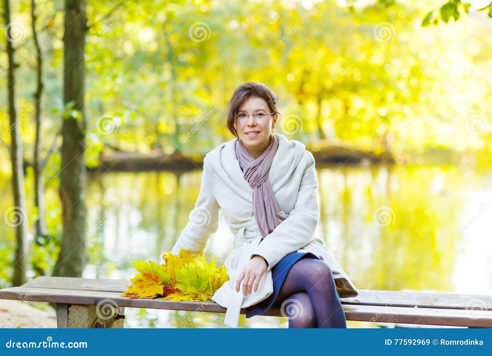 有秋天槭树的愉快的少妇在公园把诗歌选留在