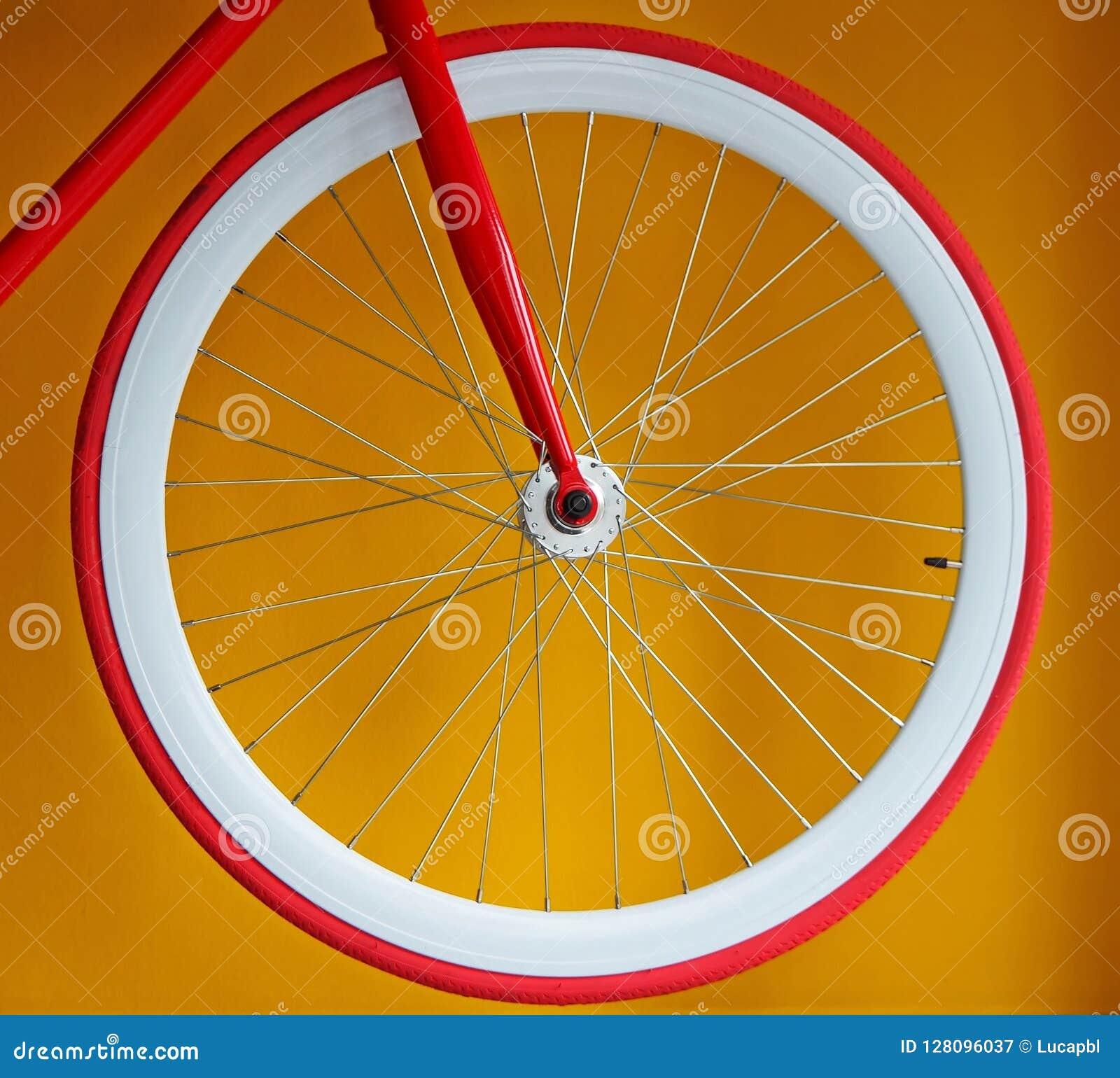 有稀薄的红色轮胎和白色宽外缘的固定的齿轮自行车车轮