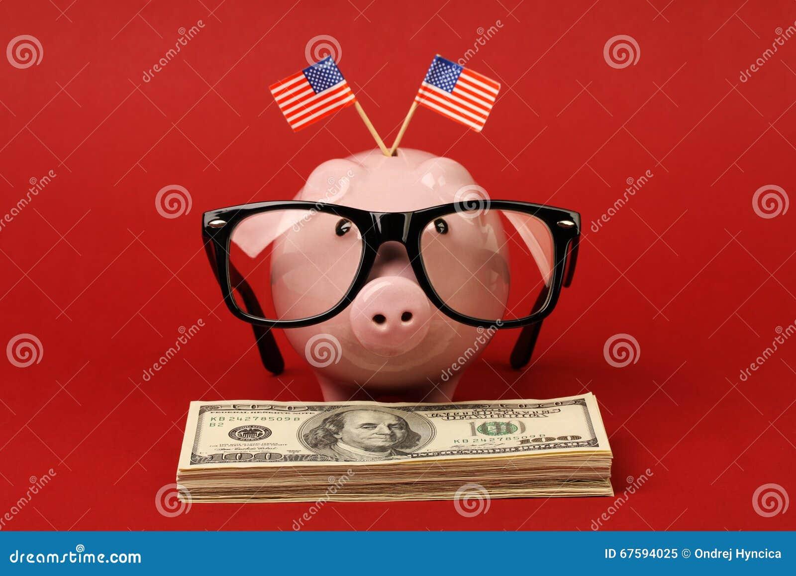 有站立在堆金钱美国人一百元钞票的玻璃和两面小美国旗子黑双孔构架的存钱罐