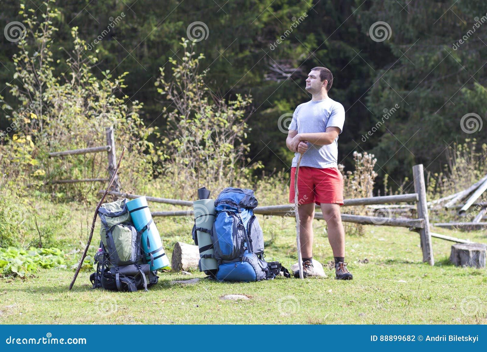 有站立在山放松和enjoyin的背包的远足者