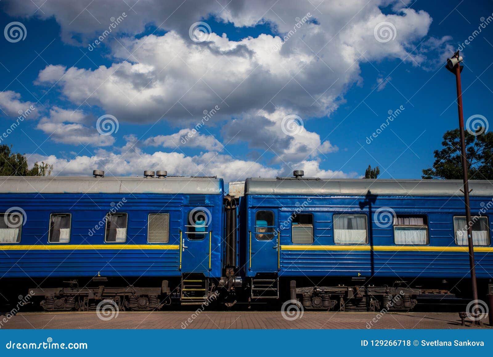 有站立在平台的蓝色无盖货车的火车反对美丽的天空背景