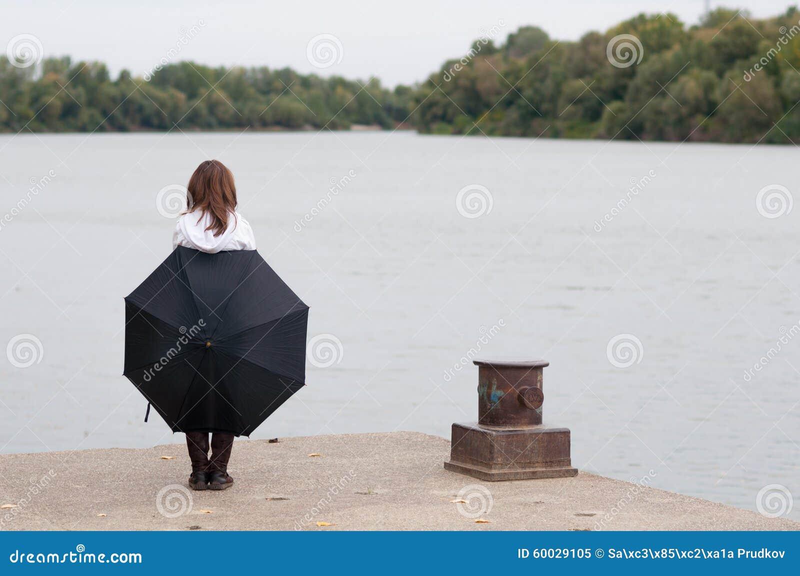 有站立在河船坞的伞的孤独的十几岁的女孩在秋天