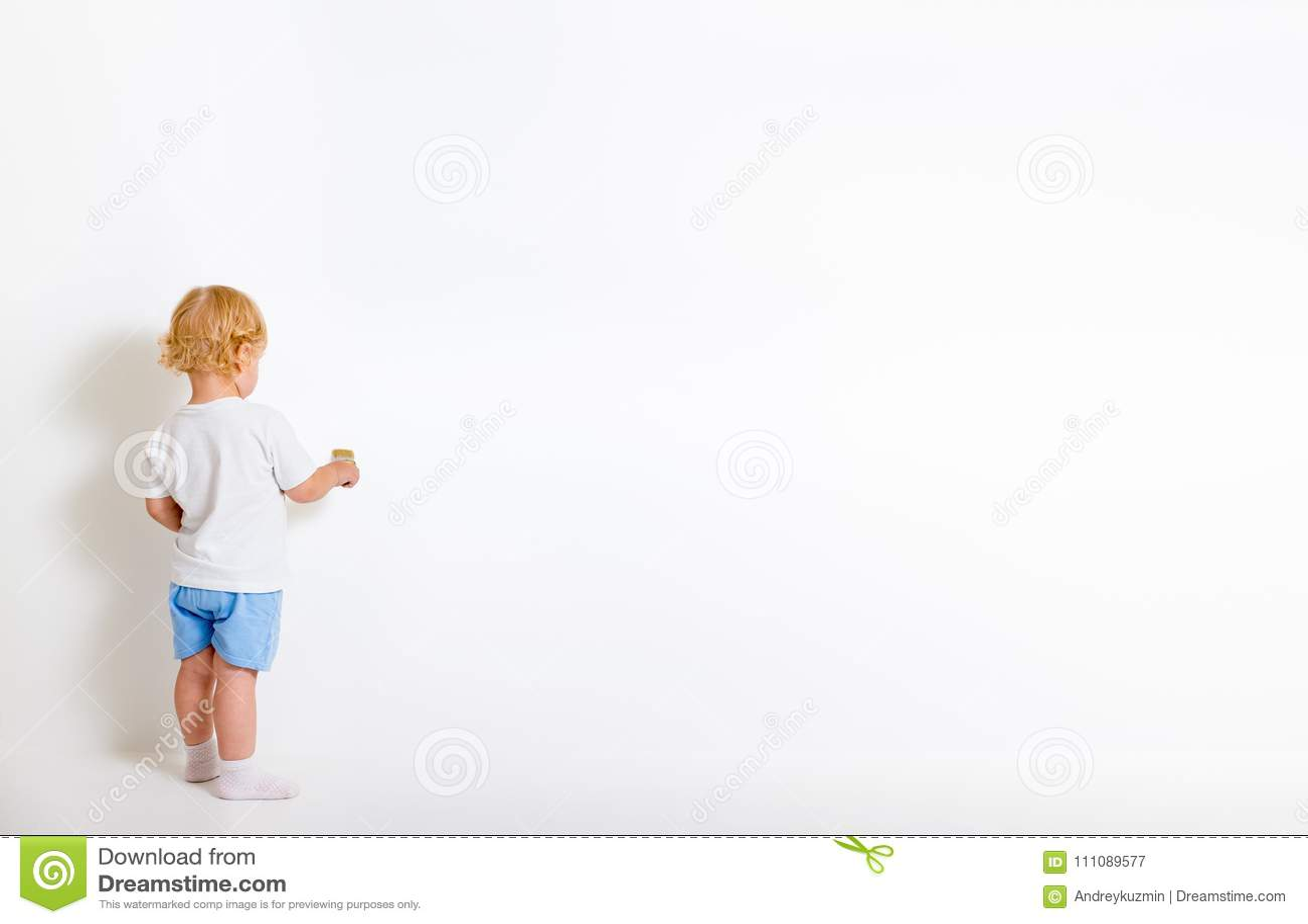 有站立在白色墙壁附近的画笔的小男孩