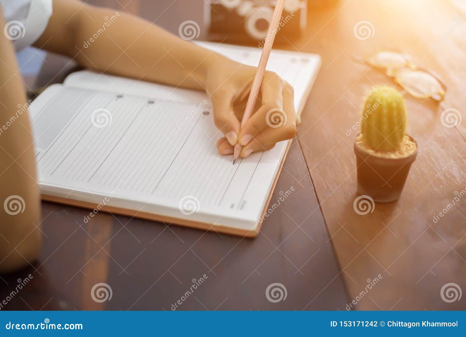有笔文字的女性手在笔记本咖啡咖啡馆