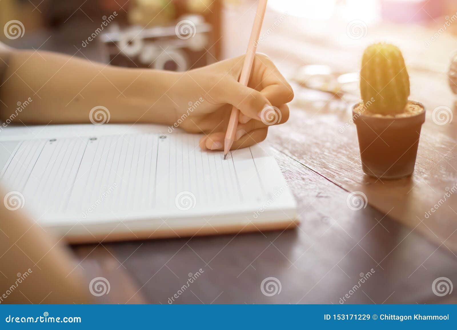 有笔文字的女性手在笔记本咖啡咖啡馆s
