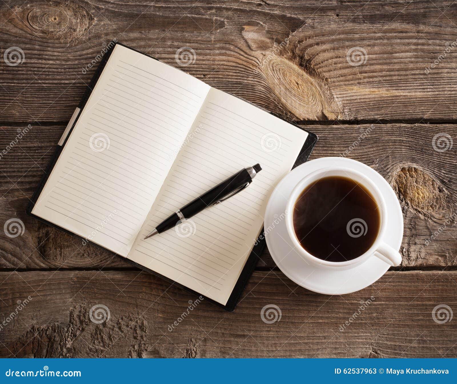 有笔的在木桌上的笔记本和咖啡
