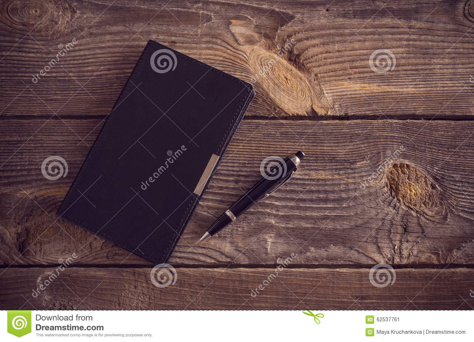 有笔的笔记本在木桌上