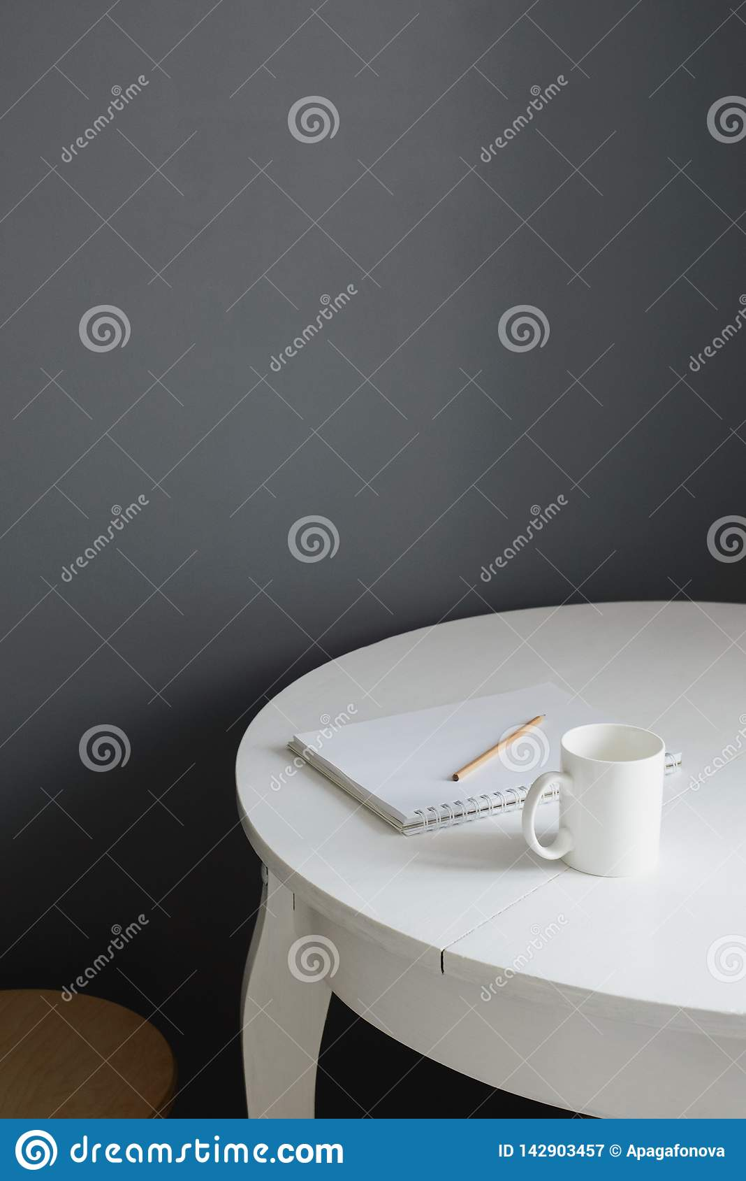 有笔记薄和铅笔的白色陶瓷咖啡杯在斯堪的纳维亚厨房内部的白色木桌上