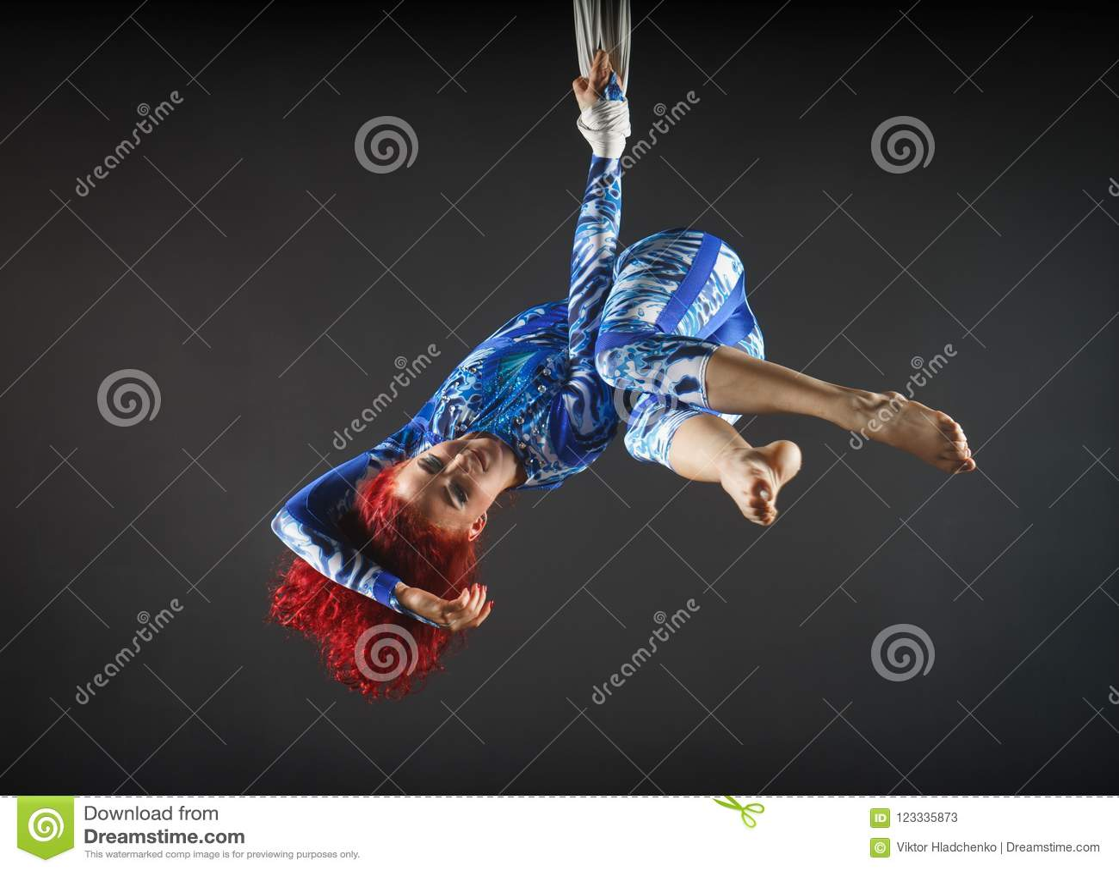 有红头发人的运动性感的空中马戏艺术家在蓝色服装跳舞在天空中与平衡