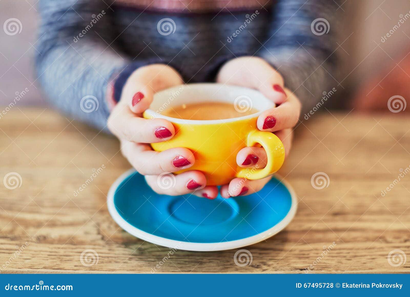 有红色修指甲和咖啡的妇女手