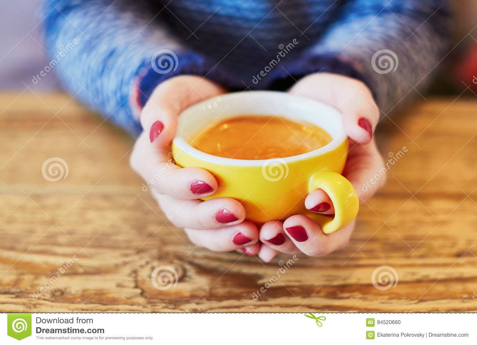 有红色修指甲和杯子的妇女手在木桌上的新鲜的热的咖啡