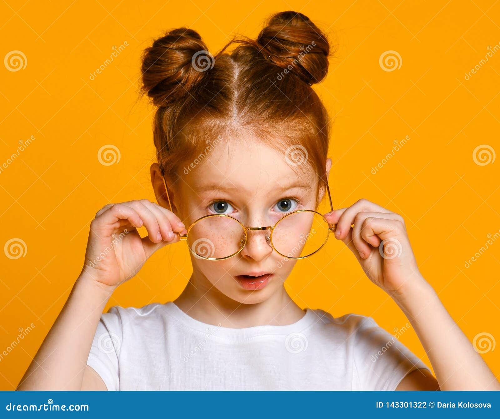 有红色头发的美丽的少女用在她时髦的玻璃的一个百吉卷看您框架的