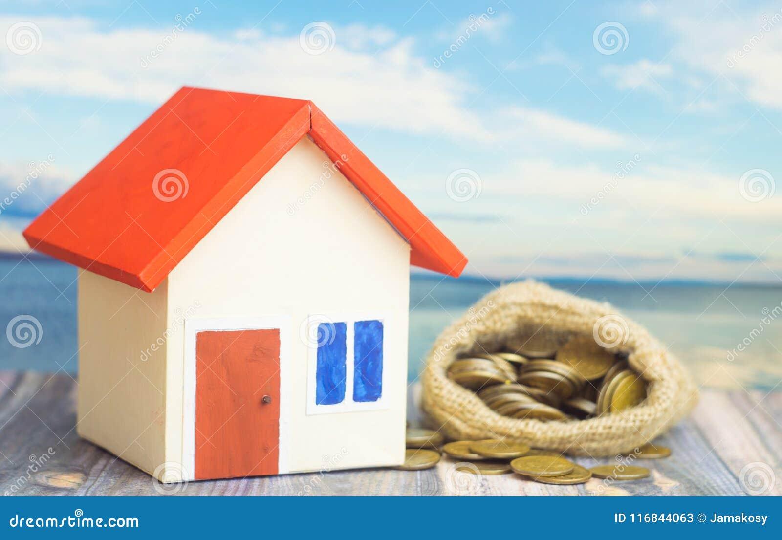 有红色屋顶的一个家在与袋子的蓝色背景从有硬币金钱的大袋在出售或购买家里面的概念