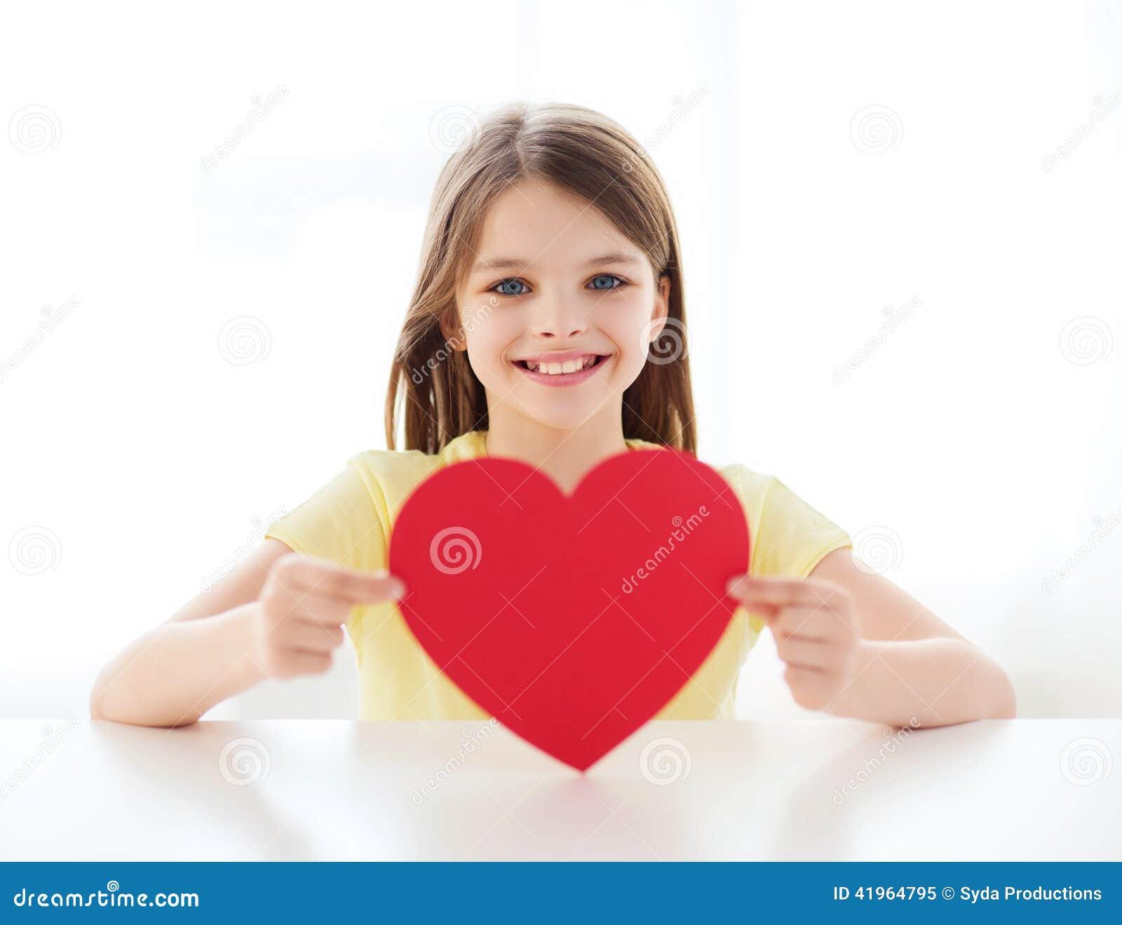 宝宝小心脏受不了图片_爱,家,幸福和人概念-有红色心脏的微笑的小女孩在家.