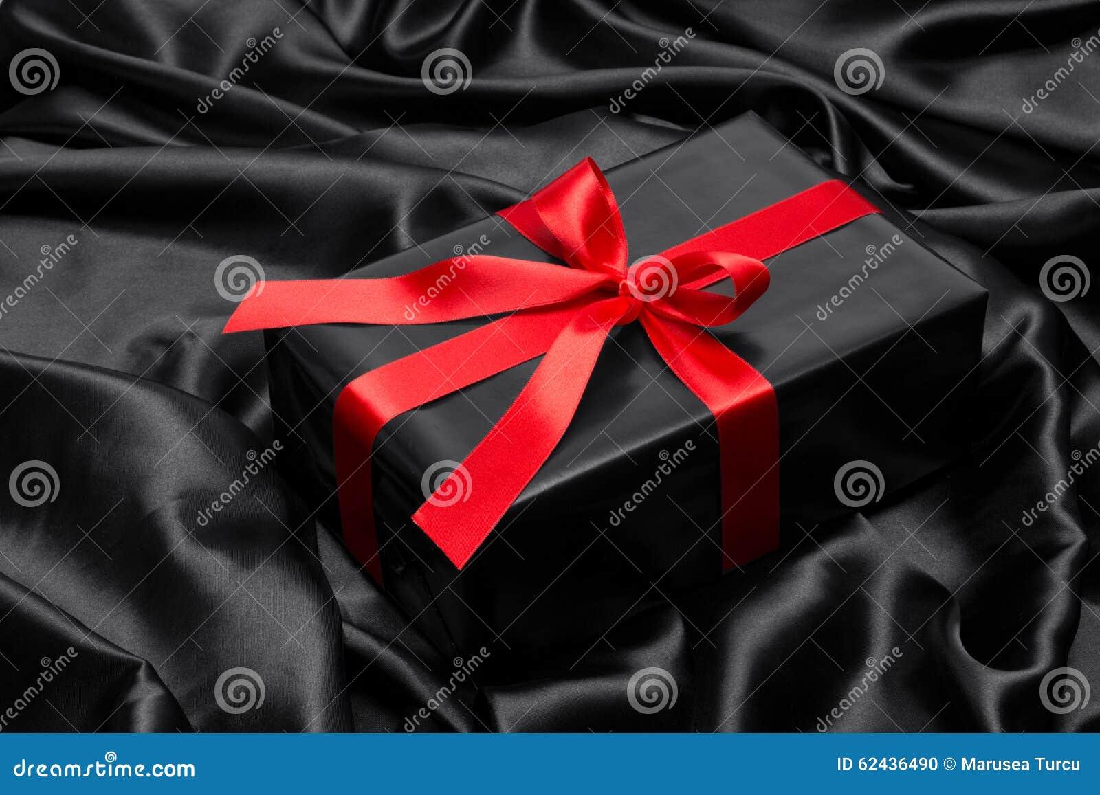 有红色缎丝带和弓的黑礼物盒