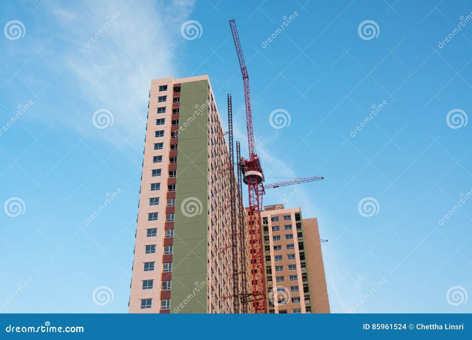 有红色起重机的楼房建筑在蓝天背景中